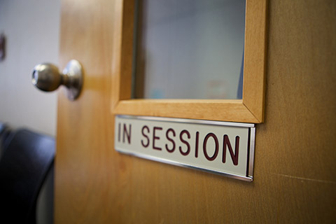 Photo of a door with a sign saying in session